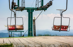 Empty ski elevator with red chairs on top of a hill. Gymba. Carpathian mountain ridge Borzhava, Ukraine. Lovely mountain landscape with clear sky Royalty Free Stock Image