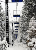 Empty Ski Lift. Surrounded by trees and snow royalty free stock photography