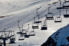 Empty ski lift above the ski slope. Stopped empty ski lift with seats above the ski slope Stock Image