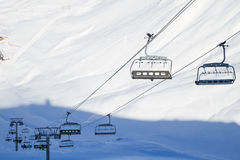 Empty ski lift, cable chair on a sunny day in ski resort. Wide angle image of a ski lift, cable, chairlift, lift in French Alps on a sunny day in mountains. Ski Royalty Free Stock Image