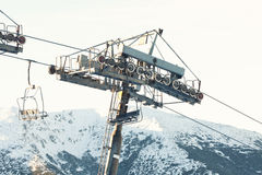 Empty ski lift chair going down from the very top of a mountain Royalty Free Stock Image