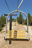 Empty ski lift chairs in a row. Many empty ski lift chairs in a row in the summer Royalty Free Stock Photography