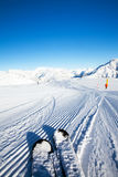 Empty ski slope. Fresh made / prepared ratrak (snowcat) snow curves under your skis and mountains panorama in the morning sunlight Royalty Free Stock Photography