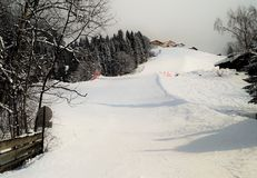 Empty ski slope. Looking up at a freshly groomed ski slope the in Austrian alps. Traditional ski chalets dot the top of the hill. No one is on the slopes yet in Stock Photos