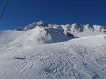 Empty ski slope. Snowy slope in the mountains with blue sky Royalty Free Stock Photography
