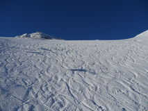 Empty ski slope. Snowy slope in the mountains with blue sky Royalty Free Stock Photos