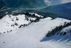 Empty ski slope. Winter landscape with empty ski slope, forest and mountains in background Stock Images