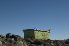 Empty skip. Rusty green skip on a building site, surrounded by rubble Royalty Free Stock Image