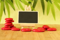 Empty slate in width to write a message that is posed on an easel with red stones columns stones on floor and in zen lifes. Small empty slate in width to write a Stock Photography