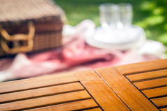 Empty slatted wooden picnic table. For your product placement with a blurred wicker picnic hamper and rug with glasses and plates on a green lawn behind Stock Photography