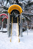 Empty slide in snow covered park Stock Images