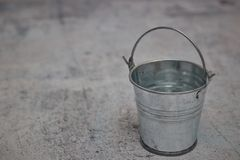 Empty small metal bucket isolated on a concrete background. copy space. horizontal view. stock image