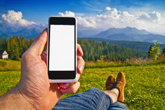 Empty smartphone screen in man's hand against landscape Royalty Free Stock Images