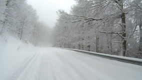 Empty snow covered road in the mountains during winter time with trees on the sides. stock footage