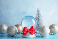 Empty snow globe with red bow and Christmas decorations. On table royalty free stock photos