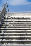 Empty snowy  stairway with sky and clouds at the top. Empty snow and ice covered slippery concrete staircase with sky and clouds at the top Stock Photo