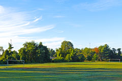 Empty soccer field with goalposts. Soccer field sunlit and crossed by tree shadows Royalty Free Stock Photography