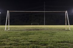 Empty soccer field at night through goal without net. Empty soccer practice field at night looking through a goal without a net down the field to the other goal Stock Photo
