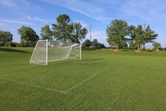 Empty Soccer Field. A view of a net on a vacant soccer pitch in morning light Royalty Free Stock Images