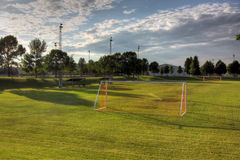 Empty Soccer Pitch. A mixed sky over an unoccupied soccer field with trees in the background. (HDR photo Stock Image