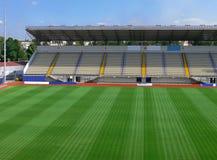 Empty Soccer Stadium 3. An empty soccer stadium with empty tribunes and grass brushed under blue sky Stock Photo