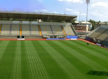 Empty Soccer Stadium 4. An empty soccer staduim with empty tribunes and grass brushed under blue sky Stock Photos
