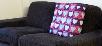 Empty sofa with purple and pink pillow covered in heart-form patches stock image