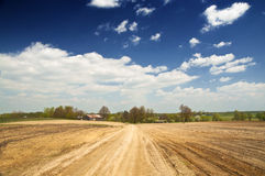 Empty soils, rural landscape. Rural spring landscape - empty field and country road Royalty Free Stock Images
