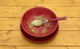 Empty soup bowl with remainder of soup. Empty soup bowl with remainder of green pea and ham soup on a wooden kitchen table Royalty Free Stock Photo