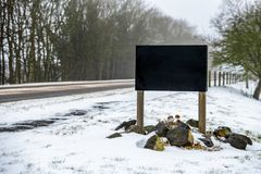 Empty space black road banner sign on winter snowy British road royalty free stock photography