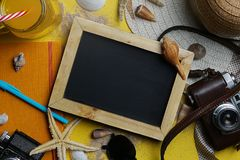 Empty Space Blackboard Between Summer Beach Accessories on Yello. W Background - Flat Lay Room For Text Royalty Free Stock Photography
