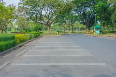 Empty space car parking lot in public park with green trees in the background. royalty free stock image