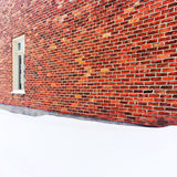 Empty space covered by snow near a brick wall Royalty Free Stock Photography