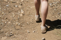 Empty space left close up of woman's feet hiking in dirt. On a sunny day Stock Image