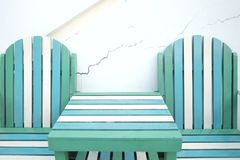 Green white wooden beach bench with table on the ground floor royalty free stock image