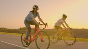 Empty Space. Sporty friends on bicycle on sunset. Couple cyclist go along coast. Sport in Nature background. Group of. People two road biker in sunset stock video footage