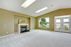 Empty spacious living room with walkout deck and fireplace. Royalty Free Stock Photography