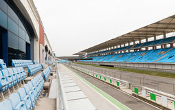 Empty speedway and bleachers on stadium Stock Photos