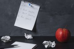 Improvements list pinned on a wall and blank notebook on a desk. Empty spiral notebook, crumpled paper and a red apple on a black desk and a page with an stock image