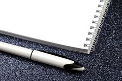 Empty spiral notebook with pen on black. royalty free stock photos