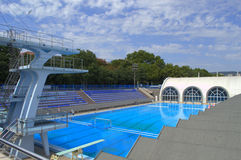 Empty sport swimming complex. Empty sport complex with outdoor and indoor swimming pool,diving tower and blue seats rows against blue sky,Varna,Bulgaria stock photography