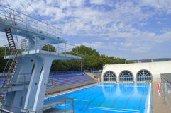 Empty sport swimming complex. Empty sport complex with outdoor and indoor swimming pool,diving tower and blue seats rows against blue sky,Varna,Bulgaria stock images