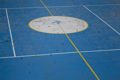 Empty sports ground with autumn leaves. Free space for sport activities - fitness, soccer, tennis. Jogging. Blue court with white lines. Retro sportsground Royalty Free Stock Photography