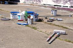 Empty spray cans and paint buckets royalty free stock photos