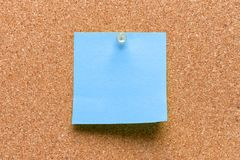 Empty square blue pinned sheet. On a brown cork reminder royalty free stock photos