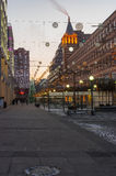 Empty square with evening illumination and occasional passers stock photo