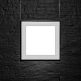 Empty square frame on black brick wall. Blank space poster or art frame waiting to be filled. Square Black Frame Mock-Up Royalty Free Stock Photo