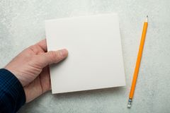 An empty square piece of paper in a man`s hand, a yellow pencil next to it. Mock-up stock image