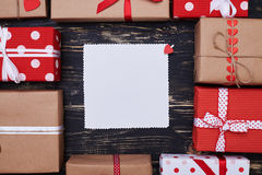 Empty square sheet of paper surrounded with gift boxes Stock Image