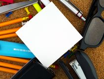Empty square sheet of white paper for your text with pencils, pen, scissor, yellow highlighter, hole puncher and glasses behind Stock Photos